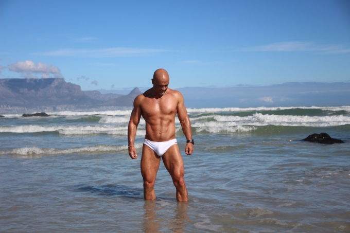MF029 Muscled bald guy with white speedo standing in water with Table Mountain in background